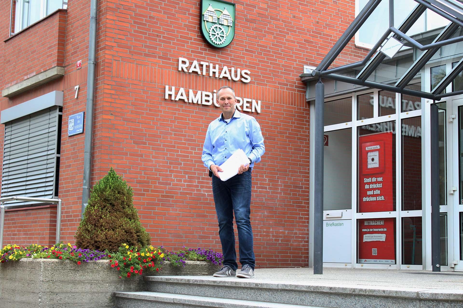 Carsten Kranz vorm Rathaus mit Bögen der Unterstützerunterschriften